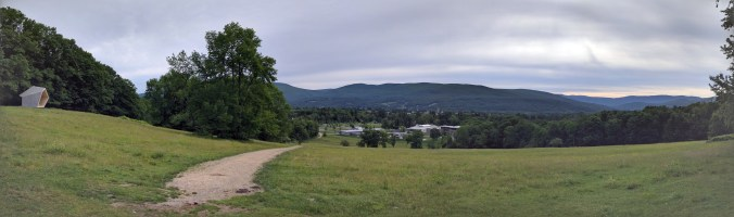 """Trail panorama showing mountains, a distant village, and the """"crystal"""" sculpture on the left."""