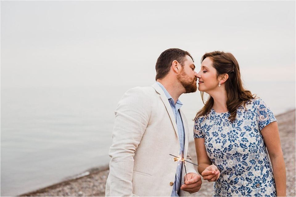couple kissing on shore of Lake Erie holding sparklers - London Stratford Cambridge Woodstock Wedding Photographer by Dylan and Sandra of Dylan Martin Photography