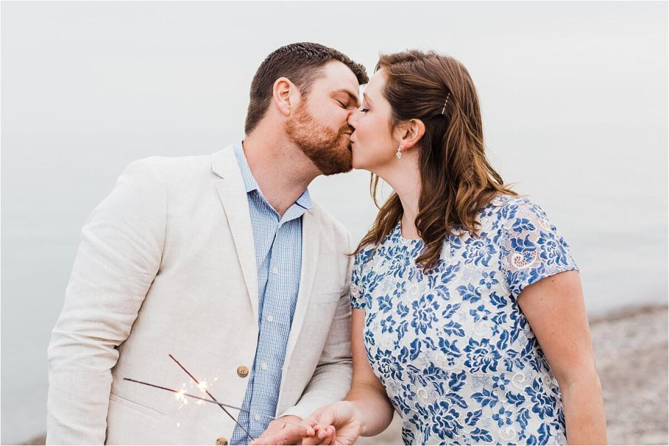 couple kissing on the beach with eyes closed while holding sparkers - London Stratford Cambridge Woodstock Wedding Photographer by Dylan and Sandra of Dylan Martin Photography