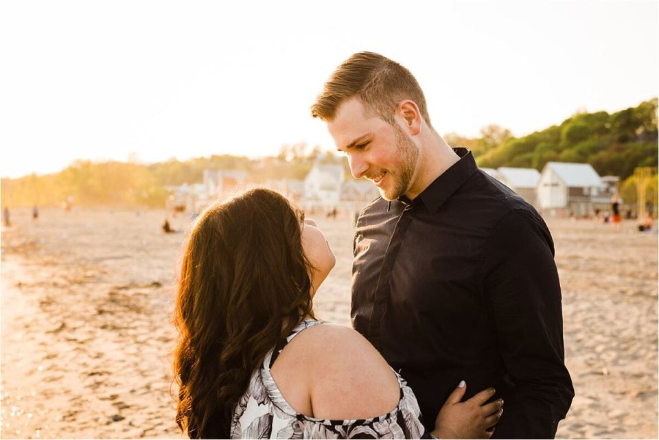 woman looking up into man's eyes and smiling while on the beach at sunset - London Stratford Cambridge Woodstock Wedding Photographer by Dylan and Sandra of Dylan Martin Photography
