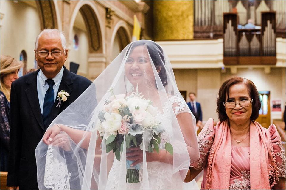 Happy bride walking to the front of the church on her wedding day Dylan and Sandra of Dyan Martin Photography for Weddings and Engagement candid photographer in London, Cambridge, Stratford and Woodstock Ontario