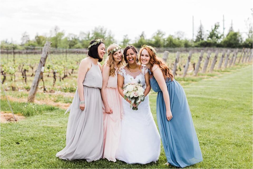 Bride and her bridesmaids laughing together on her wedding at Cave Springs Vineyard
