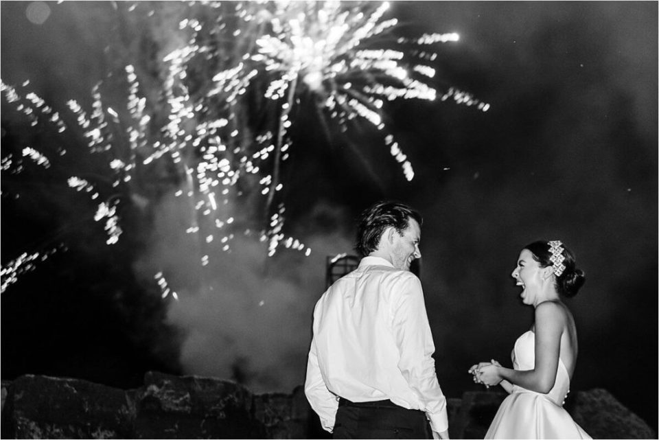 Fireworks go off behind bride and groom as they celebrate together
