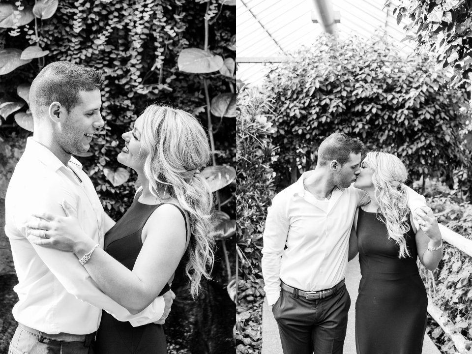 black and white photo of engaged playful couple in a greenhouse