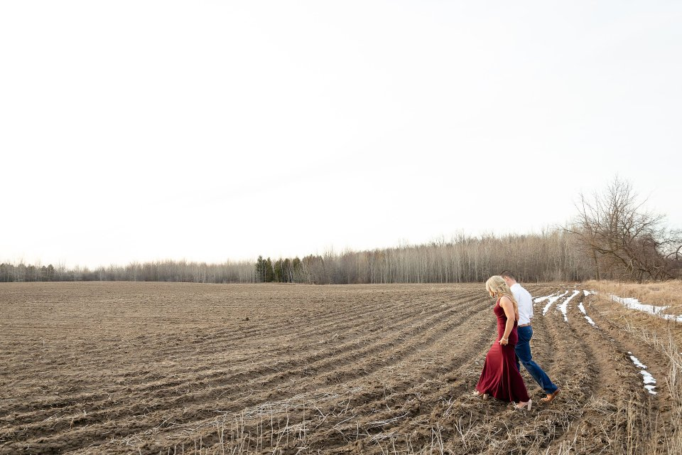 Engaged man and woman walking across the field