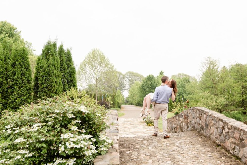 Husband carries his wife over a bridge on their 10th anniversary photo session