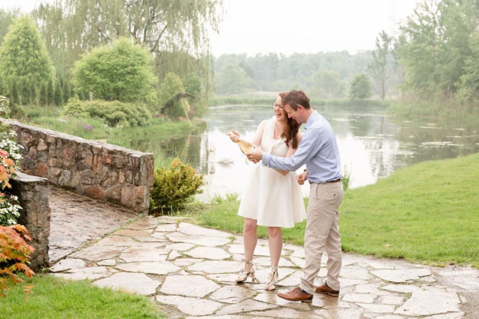 Husband and wife pop champagne together at Whistling Botanical Gardens during they anniversary session
