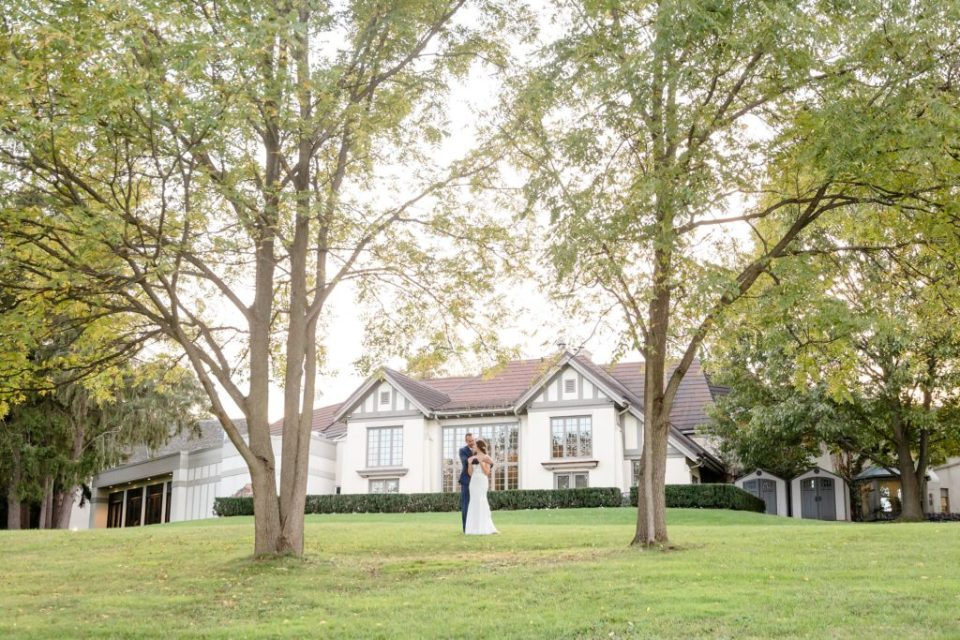 Couple standing between two large trees outside of Windermere Manor in London Ontario