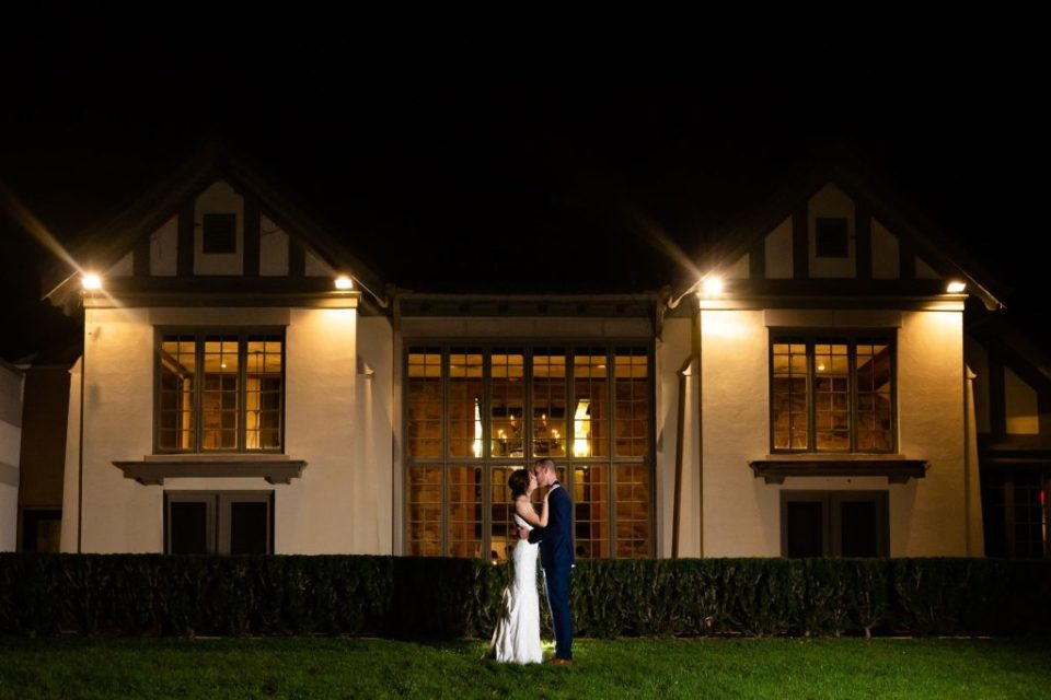 Night time photo of a couple kissing in front of the Windermere Manor Grand Hall