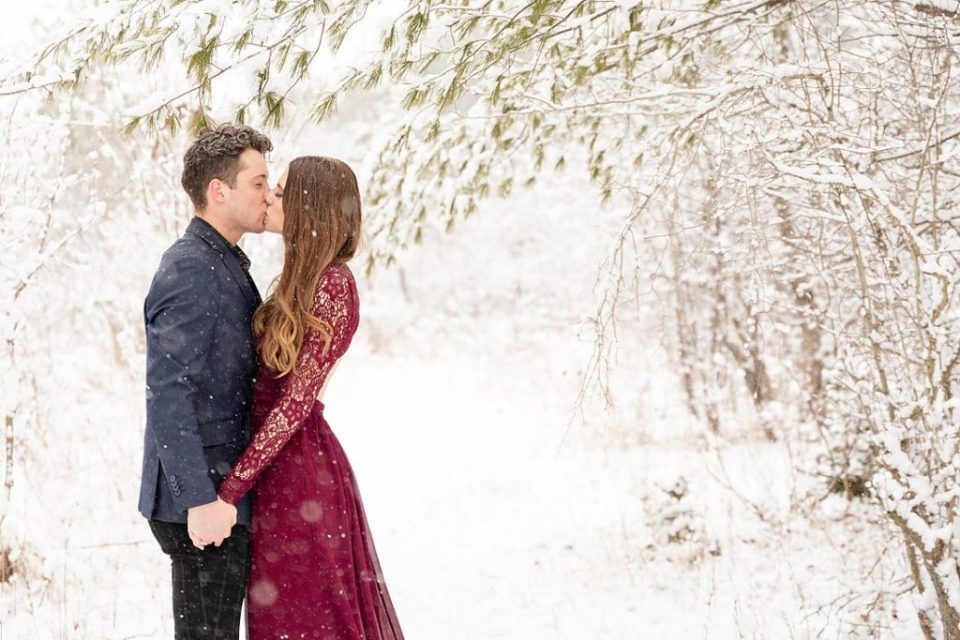 couple kissing under a tree at their winter engagement session