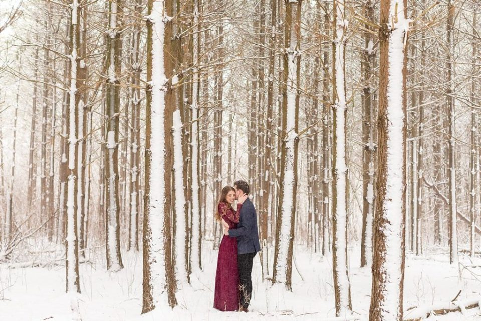 Handsome young man kissing his fiancée in a pine tree forest at winter time at Sydenham ridge estates