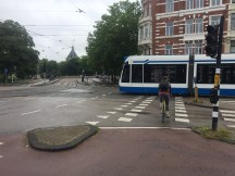 Cyclist and light rail crossing paths safely
