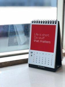 Spiral freestanding calendar on white surface:Photo byManasvita SonUnsplash.Link.