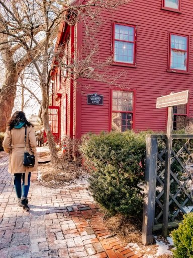 A girl in a tan coat walking by a red wooden building with a sign that says Nathaniel Hawthorne Birthplace