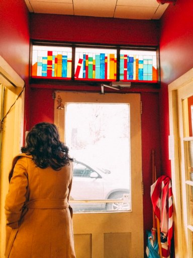 Young woman walking out a door with stained glass above it