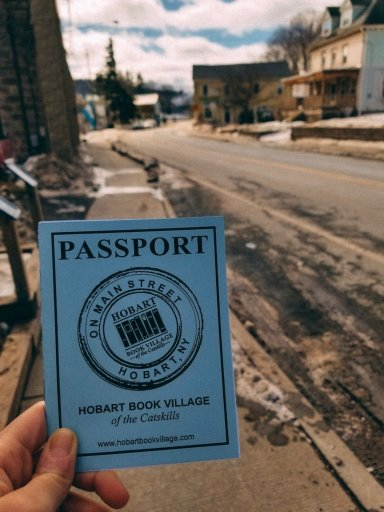 "A hand holding a blue booklet that says ""Hobart Book Village Passport'"