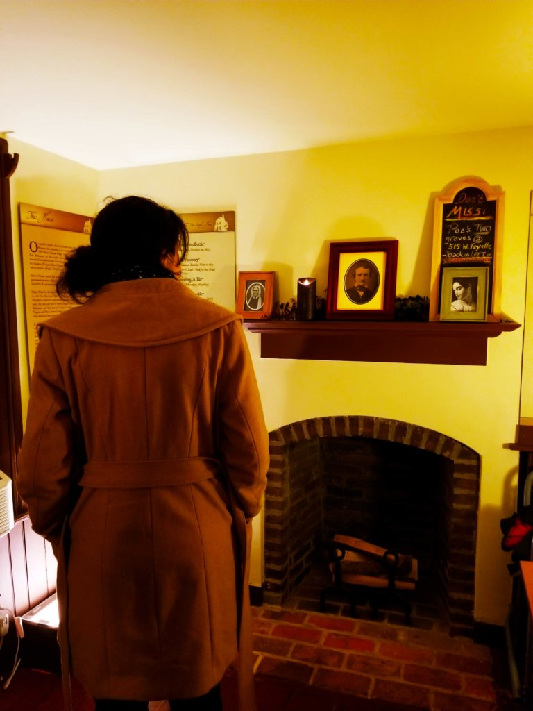The back of a young woman's head looking at a photo of Edgar Allen Poe on the mantle