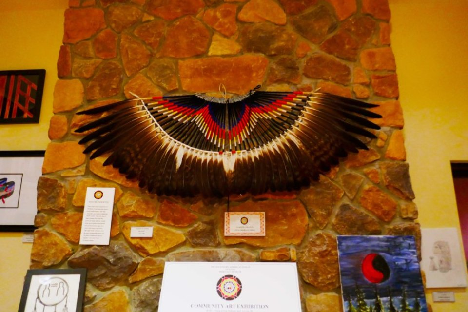 A large fan made out of feathers displayed on the wall