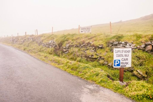 A road with green grass and a sign that says Cliffs of Moher Coastal Walk Car Park