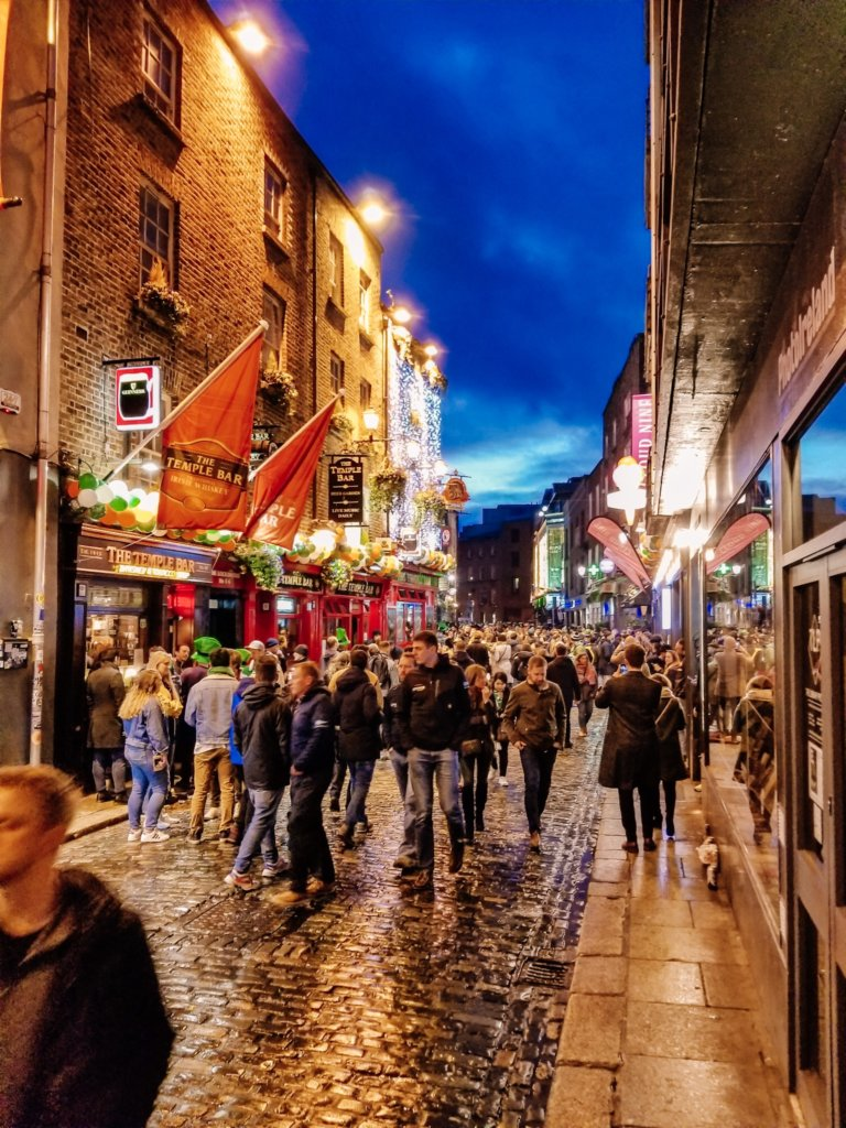 People walking down the street in Temple Bar the night before the St. Patrick's Day parade in Dublin, Ireland