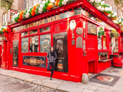 A young woman in a black coat leaning against the red wall of the Temple Bar in Dublin, Ireland during St. Patrick's Day weekend