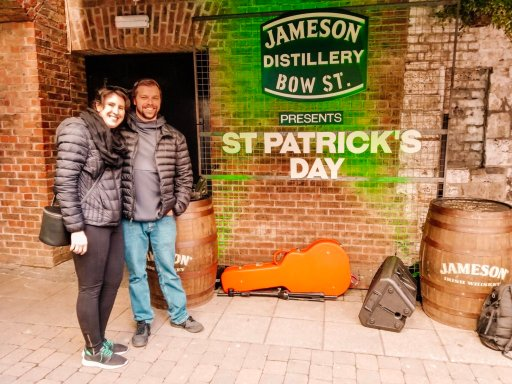 Two people standing in front of of a sign that says St. Patrick's Day in Dublin Ireland at the Jameson Distillery