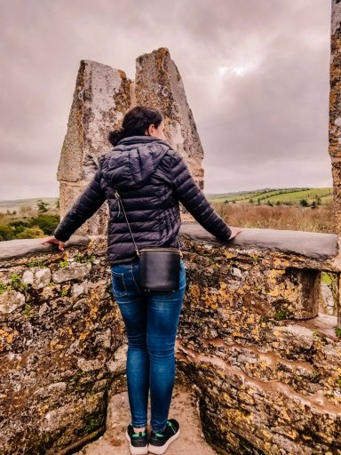 Young woman in a black jacket standing on top of Blarney Castle, looking out at the Irish countryside