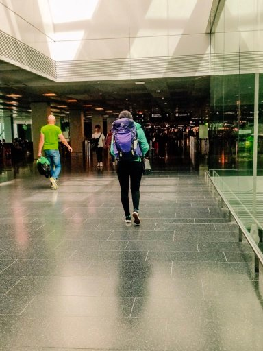 Walking through the airport with a bright purple backpack, which inspired this post on carry on packing tips