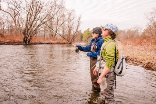 A young man and a young woman standing a  stream with a fishing pole in Berkshire County, MA with Berkshire Rivers Fly Fishing