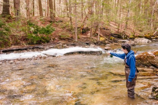 A young woman standing with a fishing pole in a river in Berkshire County, MA with Berkshire Rivers Fly Fishing