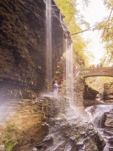 A young woman standing under a waterfall in the forest - a popular thing to do in Watkins Glen