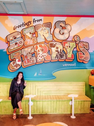 Me giving a peace sign in front of a sign that says Greetings from Ben and Jerry's Vermont