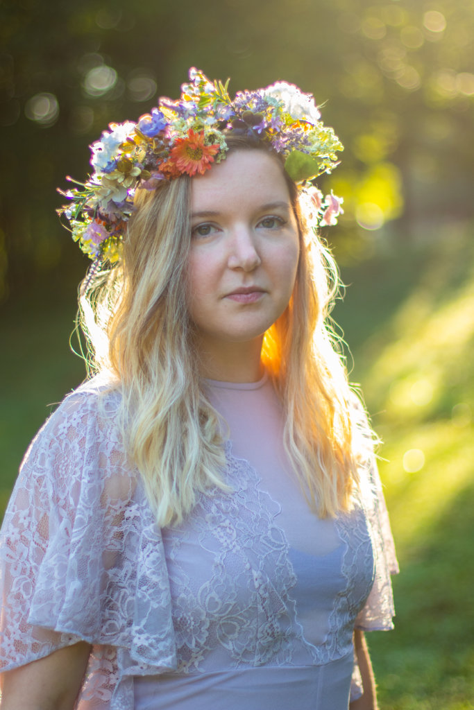 Girl in a purple dress with a flower crown illuminated by golden sun at Kilgore Falls photo shoot