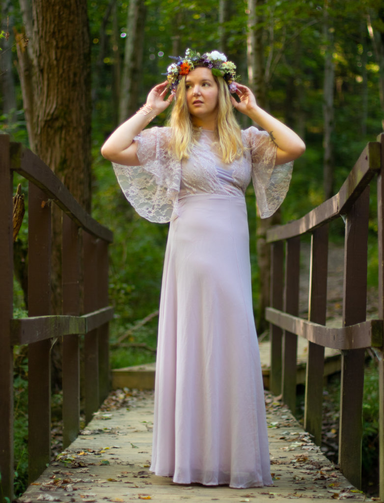 Girl in a purple dress with a flower crownstanding on a wooden bridge at Kilgore Falls photo shoot