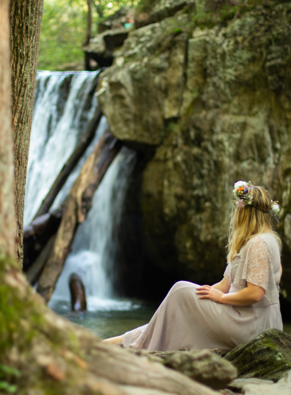 Girl in a purple dress with a flower crown sitting by the waterfall at Kilgore Falls photo shoot