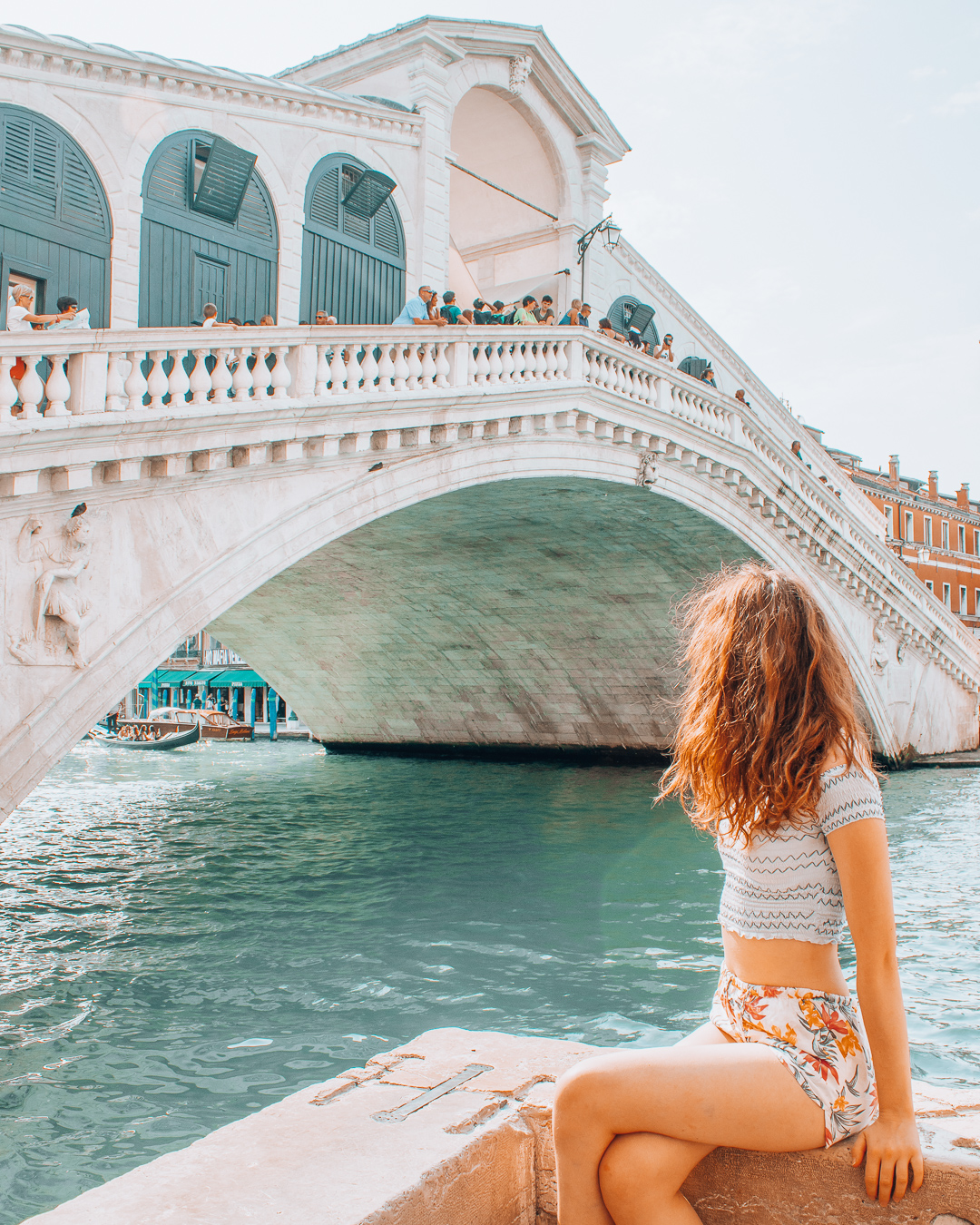 Girl looking at the Rialto bridge in Venice
