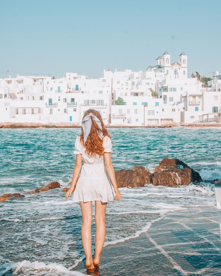 Girl looking at white houses in Paros