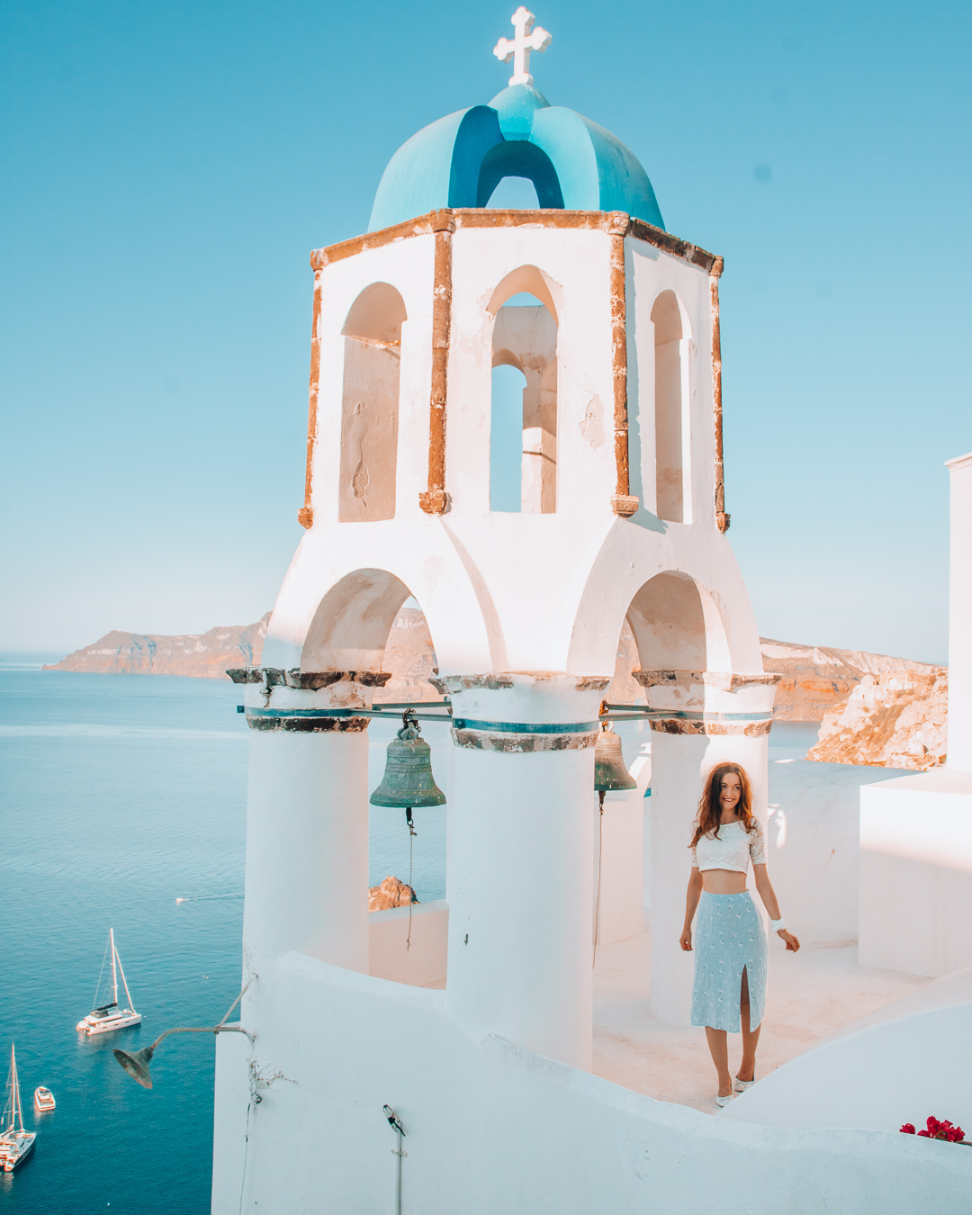 Happy girl at a beautiful bell tower in Santorini