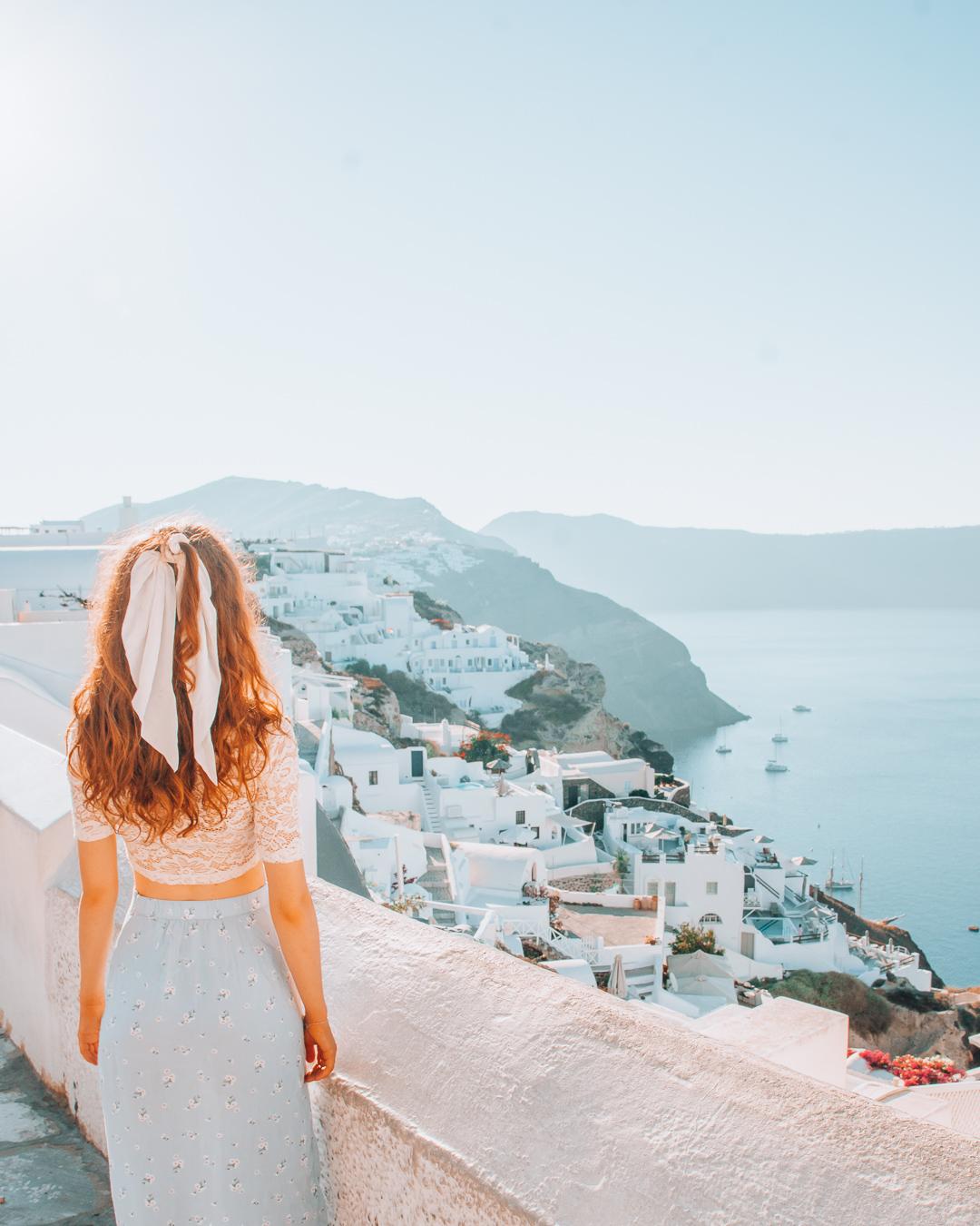Girl looking at white houses in Santorini
