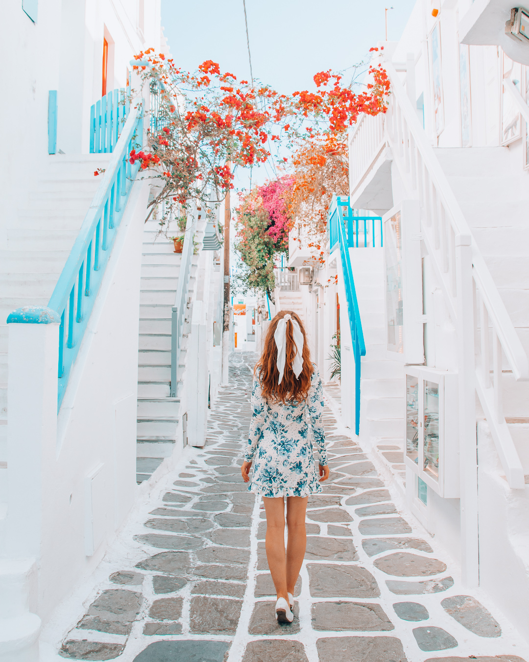 Girl walking in a street in Mykonos with cobblestones and flowers