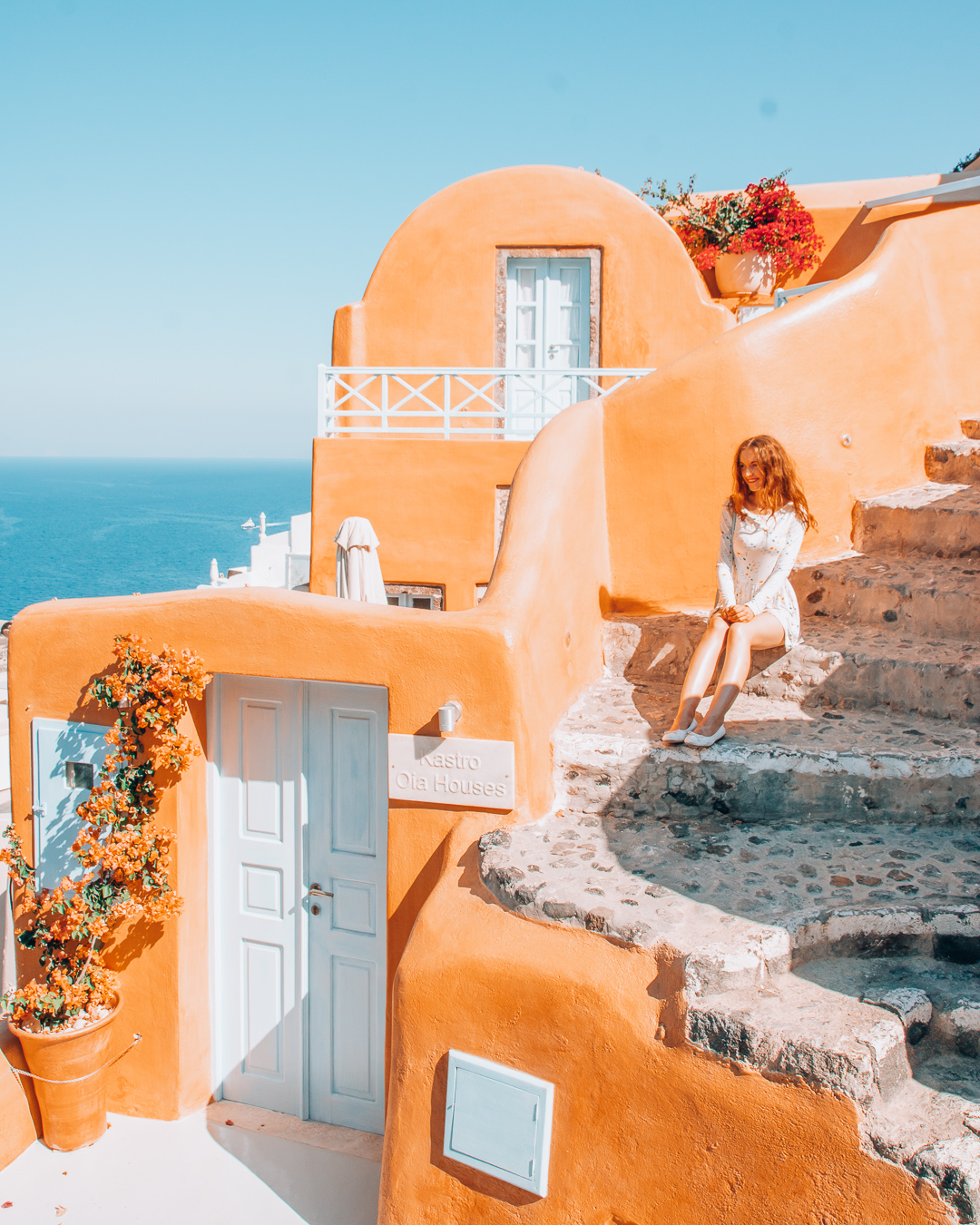 Girl sitting at the stairs of Kastro Oia Houses