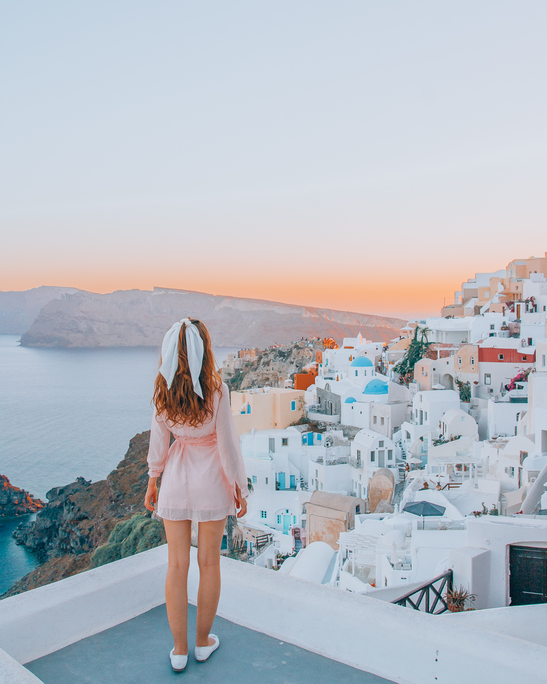 Girl looking at the view of Oia from a rooftop during sunset