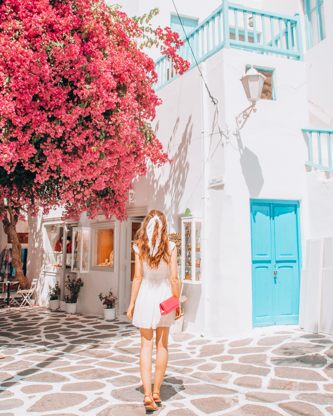 Girl with a white dress and a pink bag looking at a building and a pink tree in Mykonos