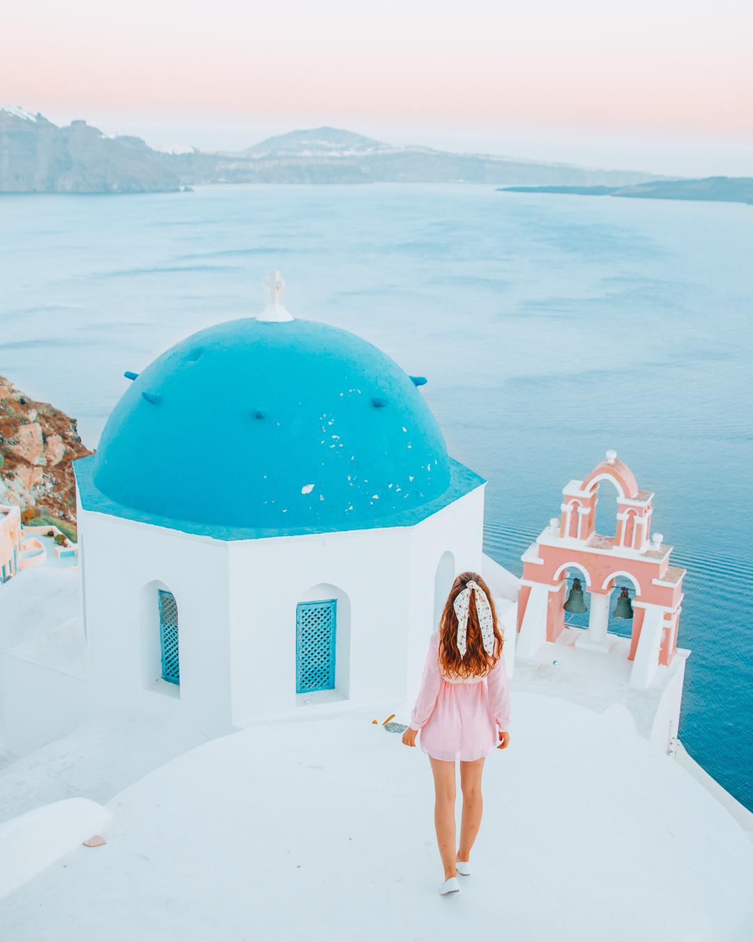 Girl in pink dress on top of Church Anastasis in Santorini
