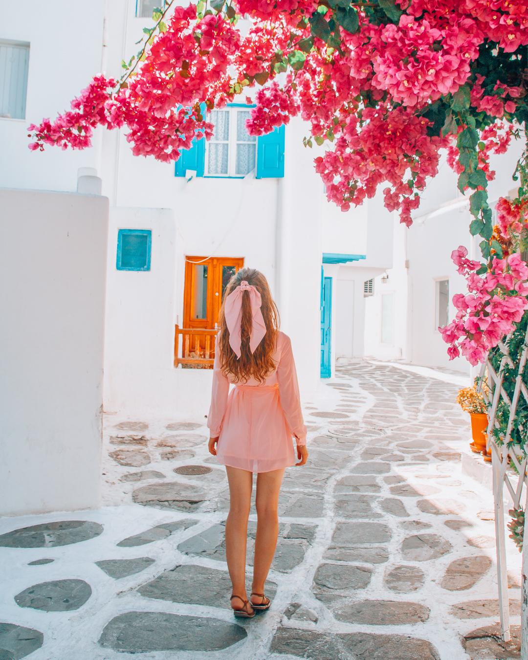Girl walking away from pink flowers in Mykonos