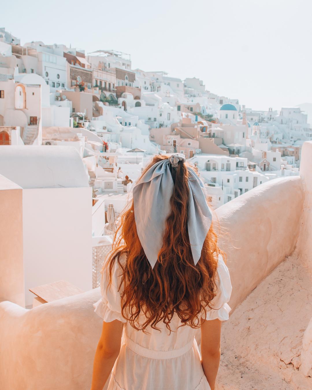Girl enjoying the view over white houses in Santorini