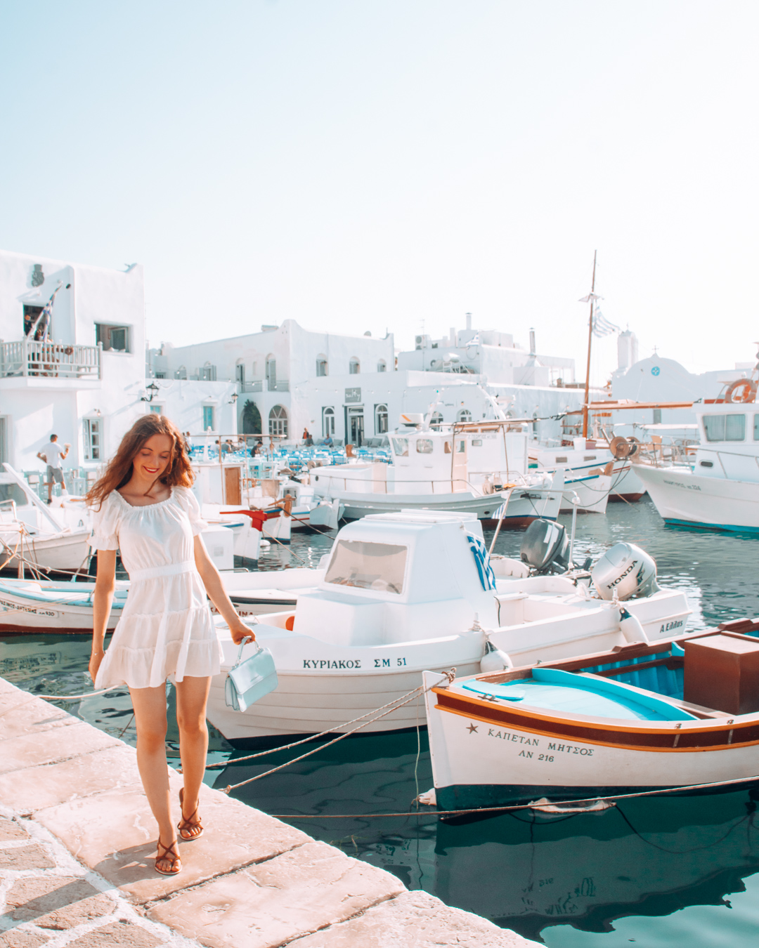 Boats and girl in the port of Naoussa
