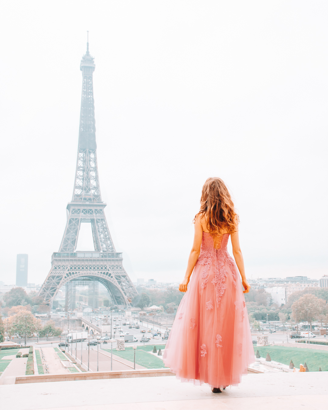 Girl in a long dress in front of the Eiffel Tower in Paris