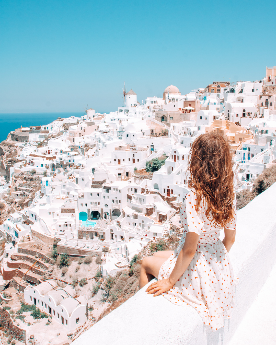 Girl sitting at Oia Castle with view over with houses