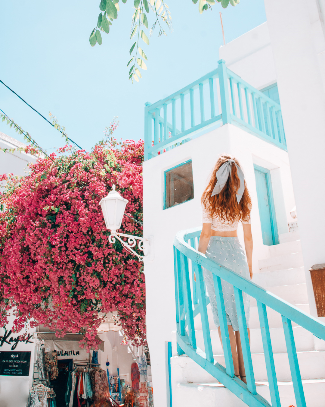 Girl on stairs in Mykonos and a pink tree